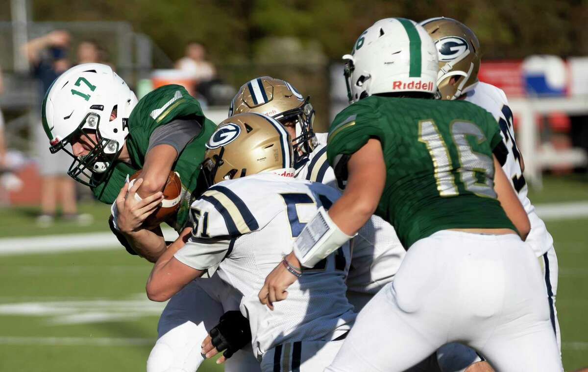 The Woodlands Christian Academy quarterback Josh Johnson (17) is tackled by multiple Boerne Geneva players during the first quarter of a TAPPS Division II bi-district game at Warrior Stadium in The Woodlands, Saturday, Nov. 21, 2020.