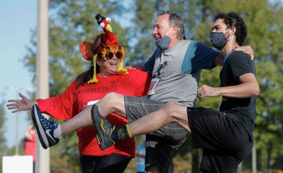 Christie Simpson, Conroe City Councilman Raymond McDonald, and Hawk Nolan have some fun before the city of Conroe's Turkey Trot at Carl Barton Jr. Park, Saturday, Nov. 21, 2020, in Conroe. More than 200 runners took part in the annual 5K race.
