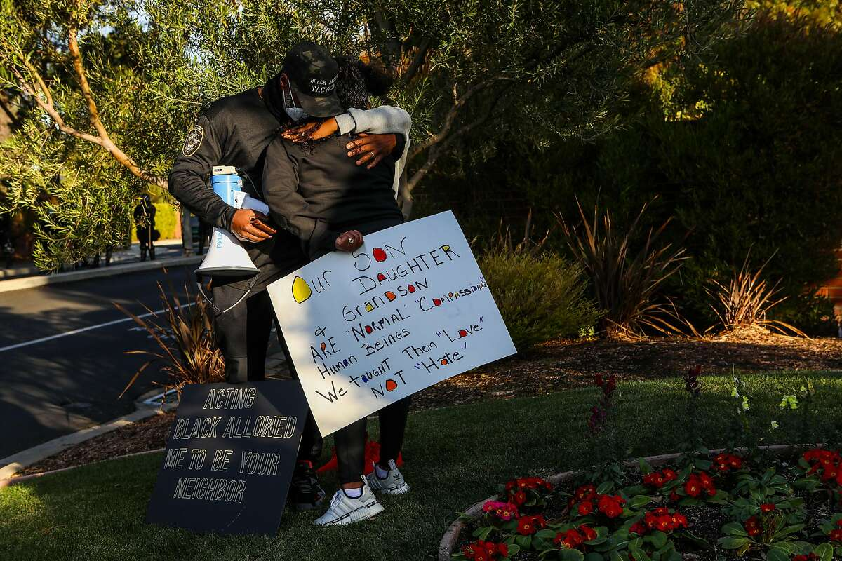 Carol Jones is comforted by her husband, Oscar Jones, and their daughter, Jariell Jones, during a march that stopped in front of the Discovery Bay Country Club on Saturday.