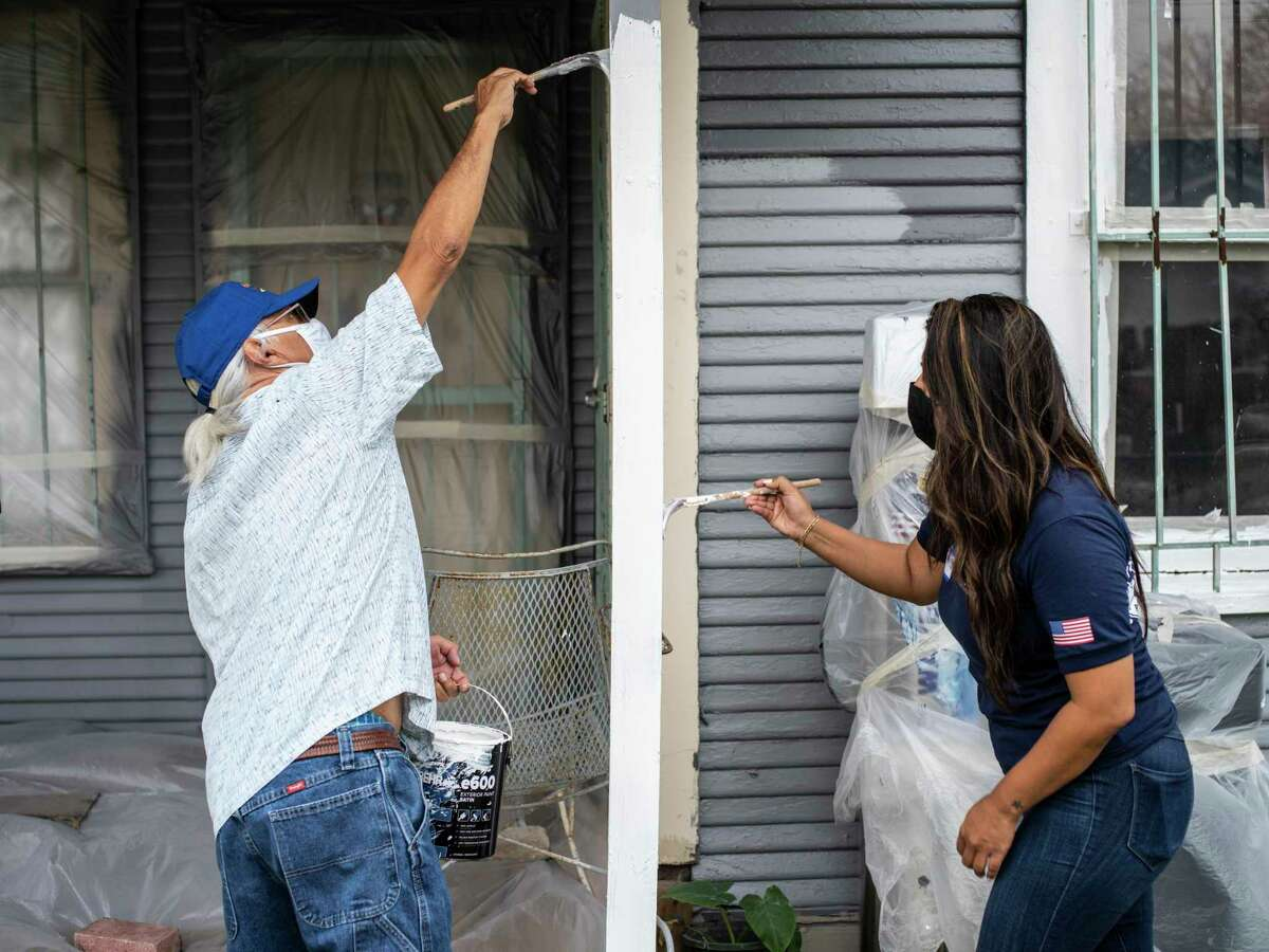Volunteers Richard Gonzales, left, and Jessica Flores, right, paint the home of Gilberto and Alicia Aleman on Saturday, November 21, 2020, on San Antonio's East Side during an Eastside Paint-A-Thon event sponsored by Neighborhoods First Alliance. The event took place as part of the nonprofit's