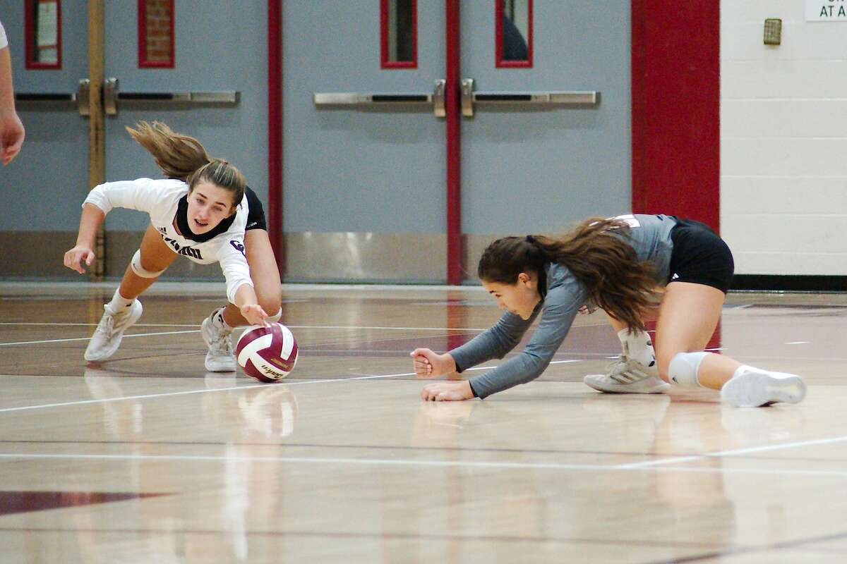 Clear Creek's Mia Sauers (8) and Clear Creek's Briana Zamora (11) dive to make a hit against Pearland Saturday, Nov. 21 at Clear Creek High School.