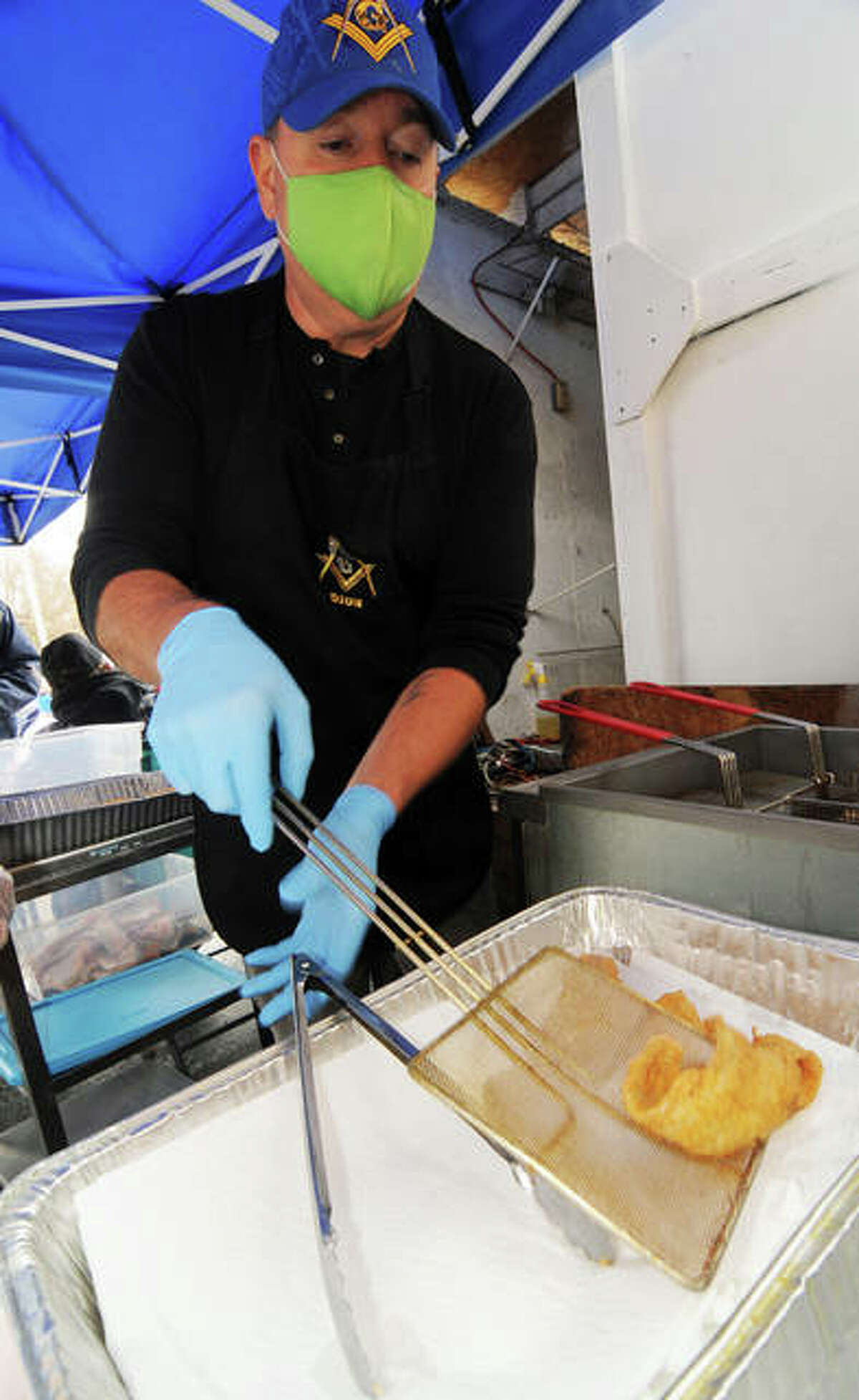 Dion Roe removes a hot piece of fish from the fryer during Saturday's Bethalto Masonic Lodge Fish Fry.