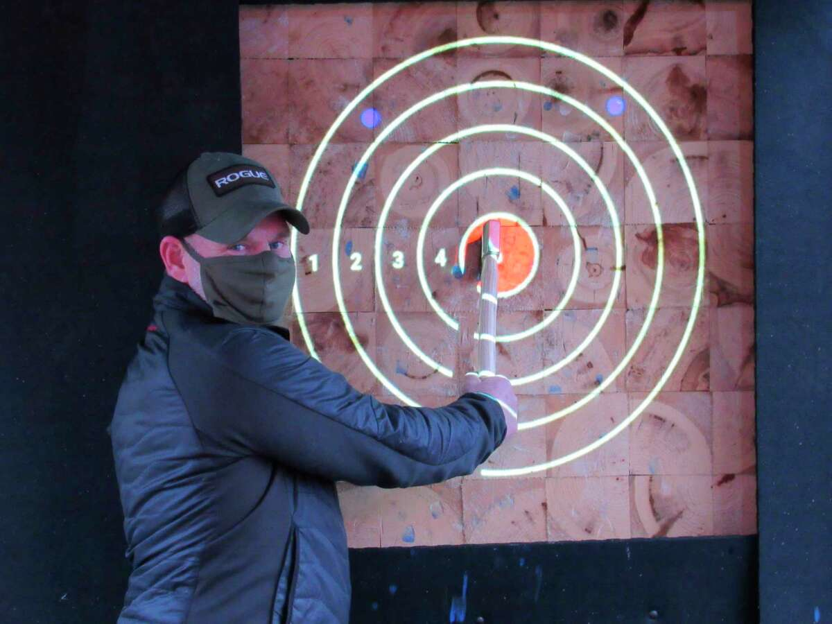 Tom Schwind of Midland poses after hitting a bullseye on Friday, Nov. 13 at Native-Axe Throwing Co. (Victoria Ritter/vritter@mdn.net)