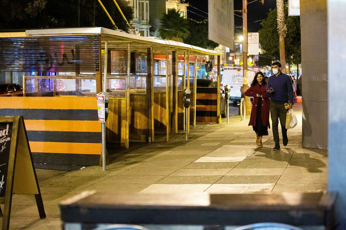 People walk along Mission Street in late November, shortly before the city entered the state's purpler tier, which put further restrictions on businesses including restaurants.