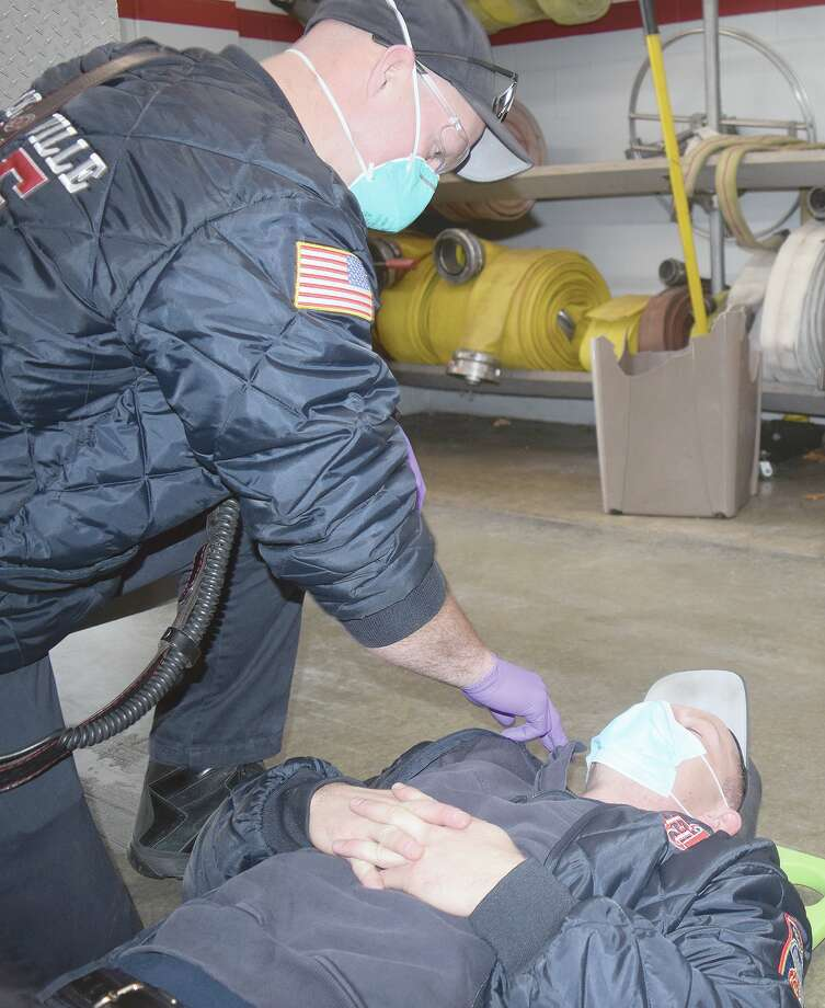 Tom Varns (left) practices response protocols with partner Chase Davis at the Jacksonville Fire Department. Photo: Samantha McDaniel-Ogletree   Journal-Courier