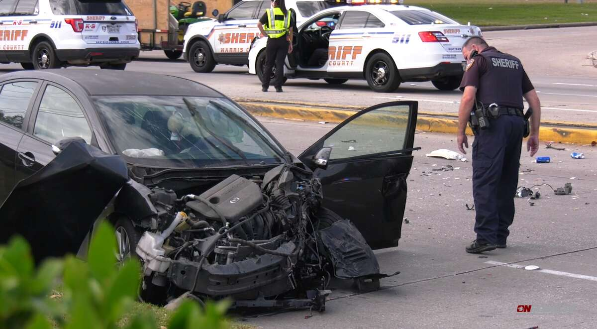 Police investigate a car that collided with a truck and killed a woman on Nov. 22, 2020.
