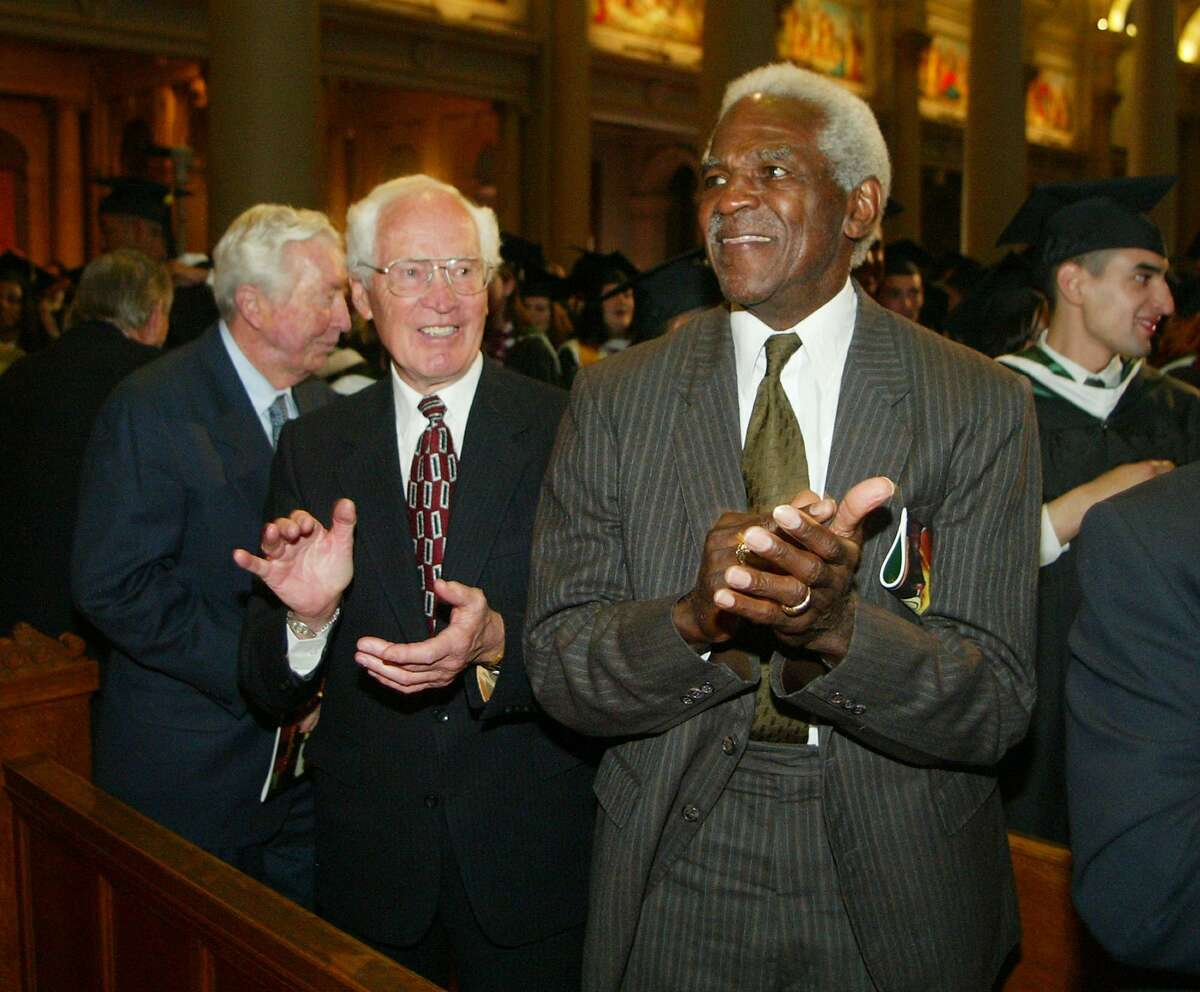 In this May 19, 2006 file photo, Burl Toler, right, and Ralph Thomas, members of the undefeated 1951 University of San Francisco football team, applaud after the school's 147th annual commencement exercises in San Francisco, where team members were awarded with an honorary degree for refusing to play a bowl game without two of their black players during the segregation era. Toler, 81, died Sunday, Aug. 16, 2009, at a hospital in Castro Valley, Calif. Toler was also the first African-American official in NFL history who went on to work one Super Bowl in a distinguished career.