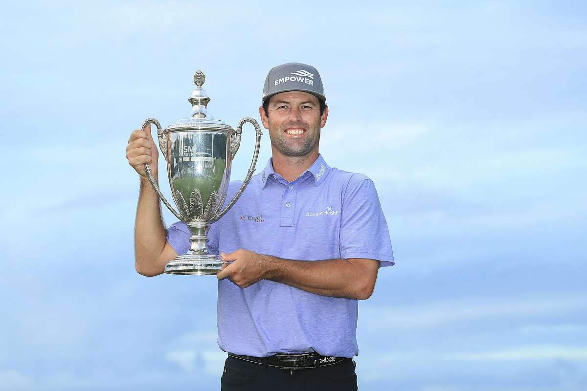 Robert Streb displays the trophy he earned by winning the RSM Classic in Georgia.
