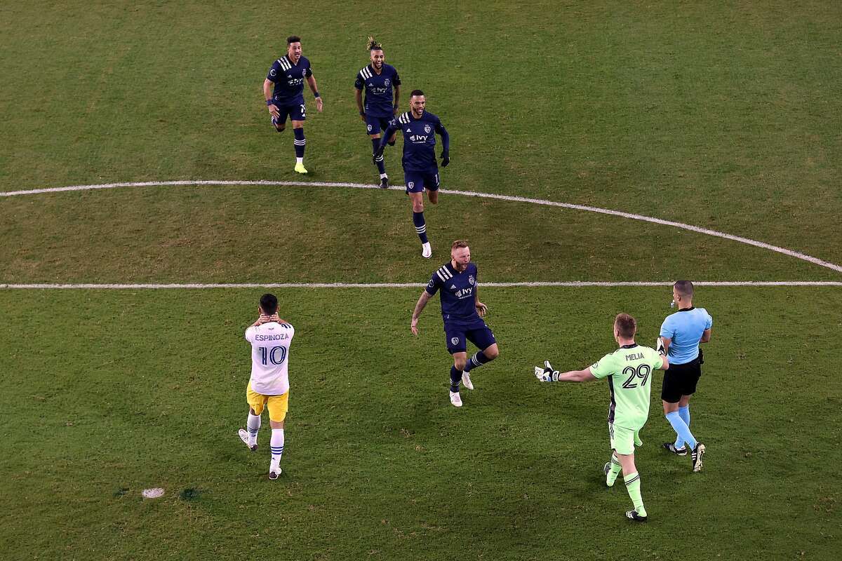Sporting Kansas City players rush to congratulate Tim Melia (29) after the goalkeeper stopped three Earthquakes penalty kicks in the shootout for a playoff win.