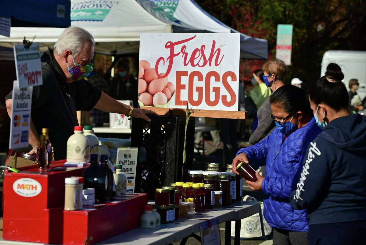Chuck Haralson of Sugar Maple Farms in Lebanon, left, helps customers shop at the last scheduled Greenwich Farmer's Market at the Exit 3 commuter parking lot at I-95 Saturday, November 21, 2020, in Greenwich, Conn. The Greenwich Farmers Market will return to its location in central Greenwich on May 15, 2021. Some vendors will be heading to Sam Bridge Nursery and Greenhouses to take part in Holiday and Winter Markets there. The Sam Bridge Holiday Farmers Market will run from 9:30 a.m. to 1 p.m. on Saturdays from Nov. 28 to Dec. 19. The market will be held outdoors.