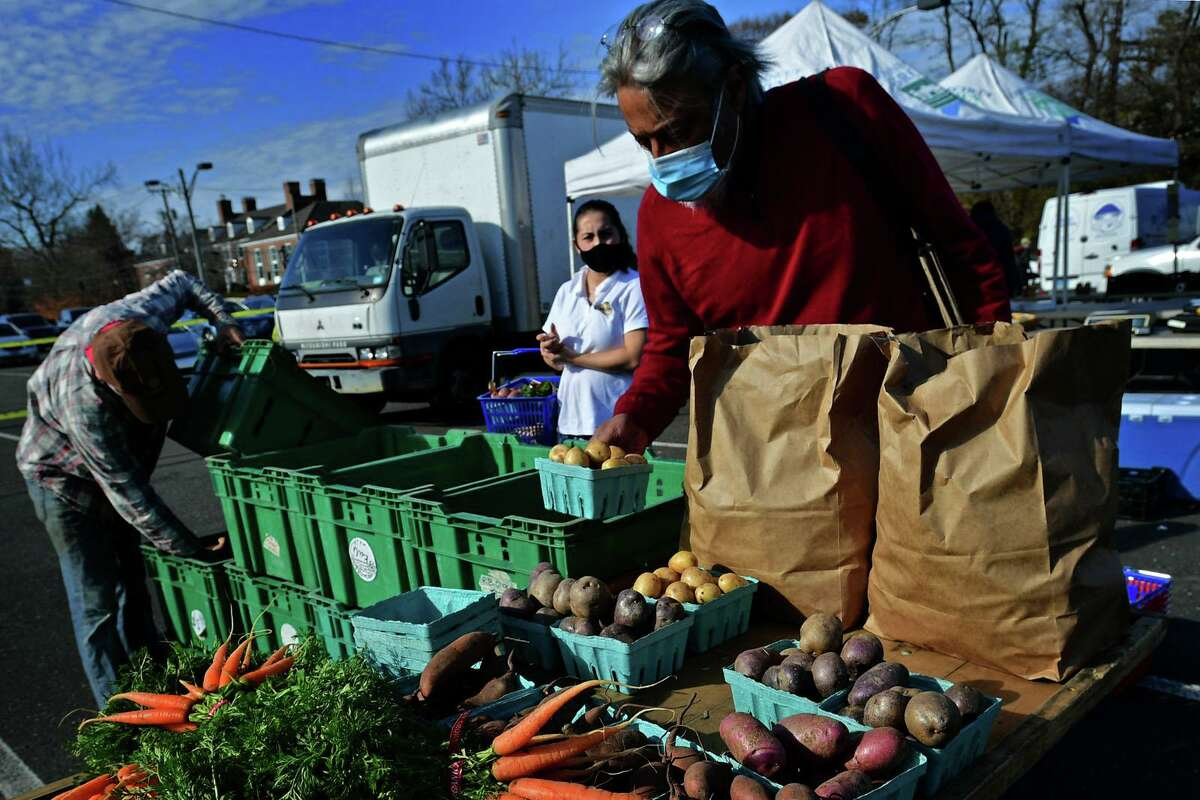 Local residents including Sanjay Santhanam shop at Riverbank Farm of Roxbury during the last scheduled Greenwich Farmer's Market at the Exit 3 commuter parking lot at I-95 Saturday, November 21, 2020, in Greenwich, Conn.