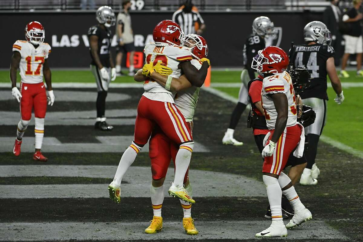 Chiefs tight end Travis Kelce embraces wide receiver Tyreek Hill after Kelce scored winning touchdown against the Raiders.