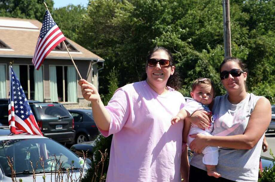 Sisters, Daniela Kalapir, left, and Sabrina Cianci, both Bridgeport, watch the annual CT United Ride drive down Main St. in Trumbull on August 29, 2010. Cianci holds her niece, Liliana, 6 months. Photo: B.K. Angeletti / Connecticut Post