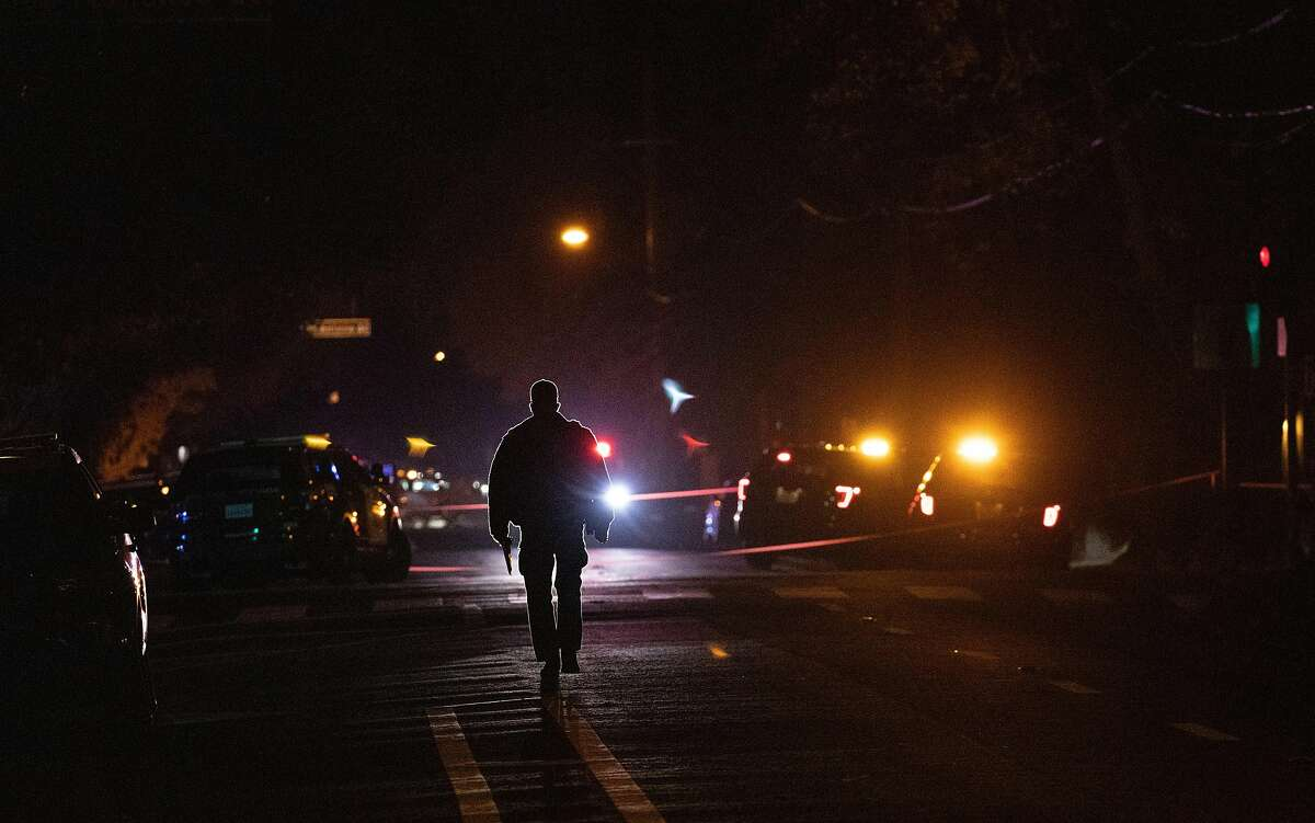An officer walks near the crime scene on 11th Street as the San Jose Police Department investigates a multiple stabbing incident at Grace Baptist Church on Sunday, Nov. 22, 2020, in San Jose, Calif.