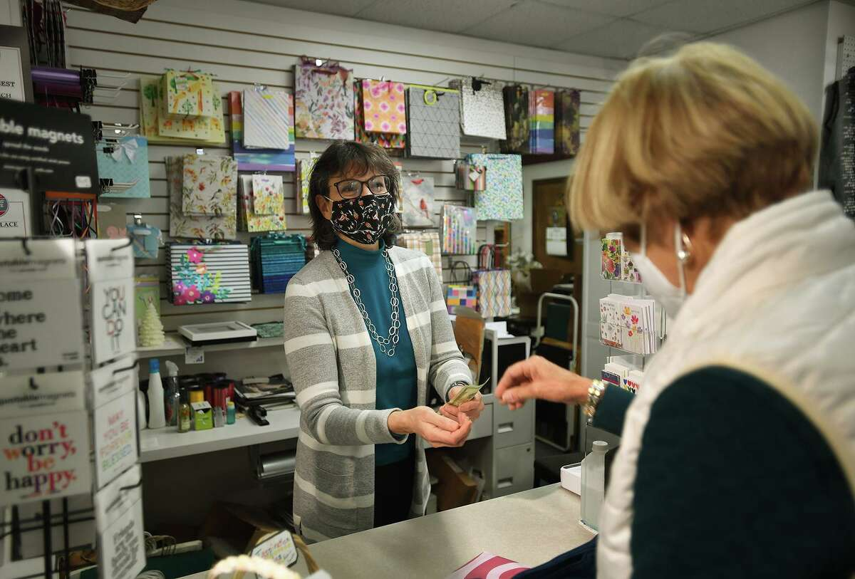 Owner Anita Bruscino waits on customer Sara Buell, of Cheshire, at Elegant Touch Fine Gifts in Cheshire Nov. 19, 2020.
