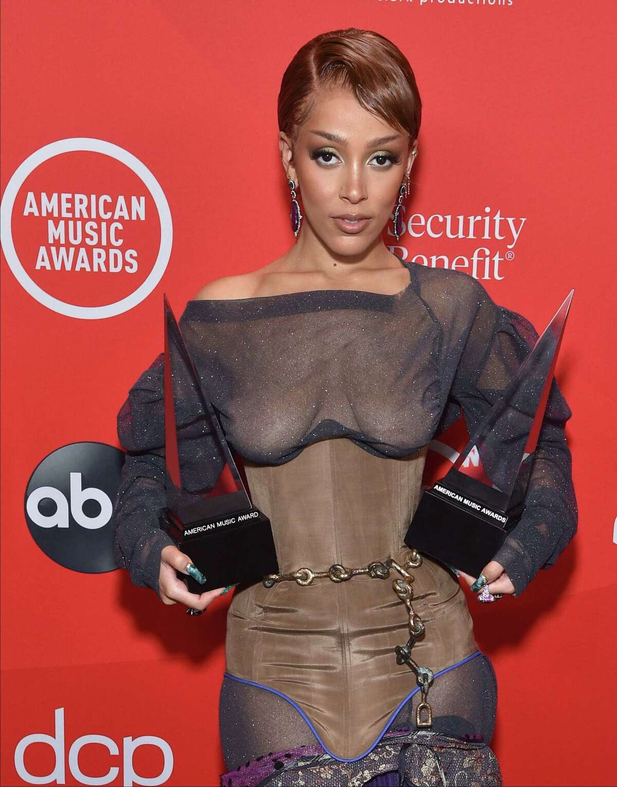 """In this handout image courtesy of ABC singer Doja Cat poses with her awards for Favorite Female Artist Soul/R&B and New Artist of the Year during the 2020 American Music Awards aired from the Microsoft theatre on November 22, 2020 in Los Angeles. (Photo by ABC / American Broadcasting Companies, Inc. / ABC / AFP) / RESTRICTED TO EDITORIAL USE - MANDATORY CREDIT """"AFP PHOTO / Courtesy of ABC"""" - NO MARKETING - NO ADVERTISING CAMPAIGNS - DISTRIBUTED AS A SERVICE TO CLIENTS"""