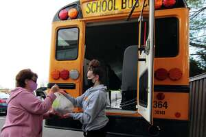 Pat DelVecchio, of Milford, left, makes a donation of food to Jonathon Law student volunteer Makenna Sharpe during the Stuff-A-Bus Food Drive for the Milford Food Bank at Shop Rite parking lot in Milford on Saturday Nov. 21. The drive was organized by bus drivers with Durham School Services of Milford.
