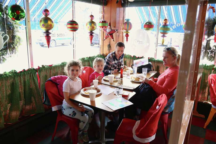 """The Sekerak and Cembrzynski families of Norwalk enjoy the partitioned off space to eat inside the Sugar Bowl Luncheonette on Saturday afternoon. """"Are we concerned? Yes,"""" said Carmen Vertula, general manager at The Goose American Bistro and Bar. """"If they're planning on shutting us down again, I don't think we can make it,"""" she said. """"We do make our profits with the indoor dining.""""  Photo: Jarret Liotta For Hearst Connecticut Media / Jarret Liotta / ©Jarret Liotta 2020"""