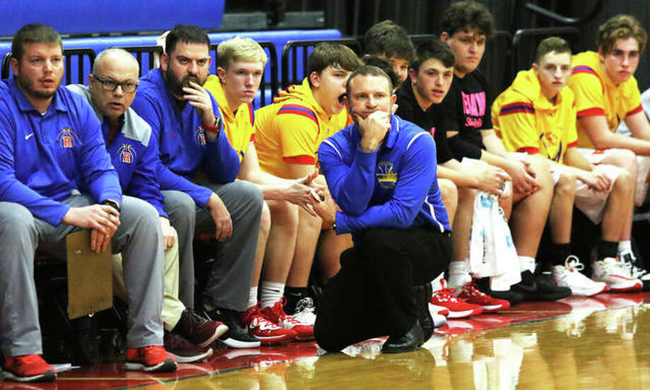Roxana coach Mark Briggs (kneeling) watches his team during a Feb. 11 South Central Conference boys basketball game against Pana last season at Milazzo Gym in Roxana. The Shells won the game and went on to share the SCC title with Pana. Now, Briggs has a proposal the help salvage a basketball season in 2021. Photo: Greg Shashack / The Telegraph