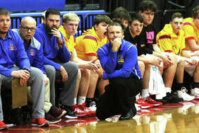 Roxana coach Mark Briggs (kneeling) watches his team during a Feb. 11 South Central Conference boys basketball game against Pana last season at Milazzo Gym in Roxana. The Shells won the game and went on to share the SCC title with Pana. Now, Briggs has a proposal the help salvage a basketball season in 2021.