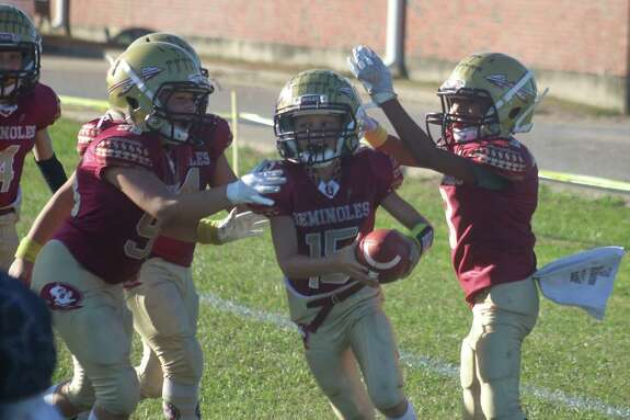 Teammates begin to mob Deer Park Freshmen Seminoles quarterback Davis Horton after Horton scored the winning touchdown in overtime, propelling the team to a come-from-behind 20-14 triumph.