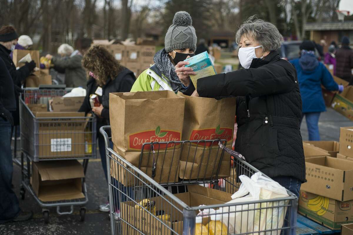 Dorothy Peters, right, loads food items into a cart for Megan Donaldson, center, as they volunteer with dozens of others during a food drive Monday, Nov. 23, 2020 at Aldersgate United Methodist Church in Midland. (Katy Kildee/kkildee@mdn.net)