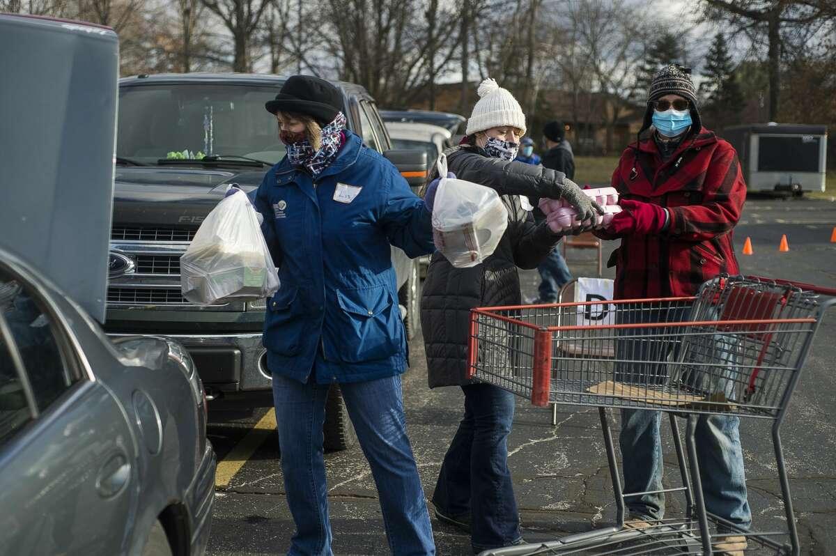 From left, Lisa McKenney, Jennifer Root and Lori Kranz load food items into vehicles during a food drive Monday, Nov. 23, 2020 at Aldersgate United Methodist Church in Midland. (Katy Kildee/kkildee@mdn.net)