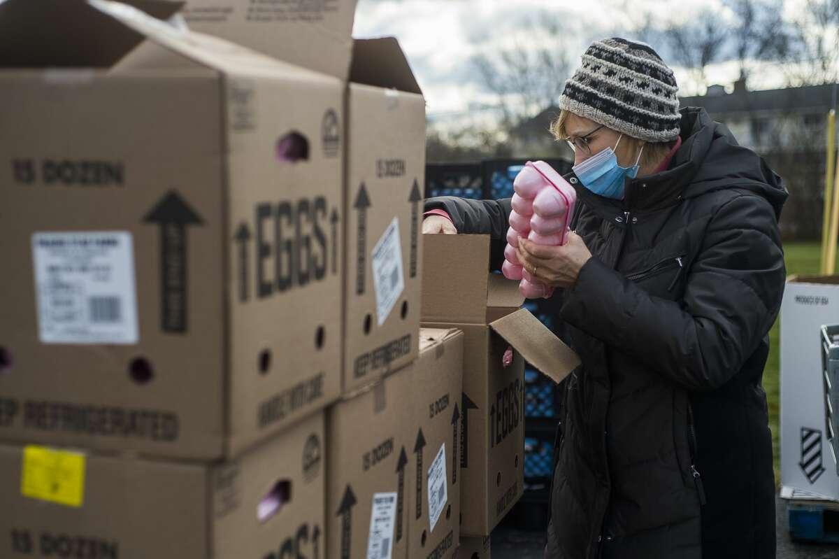 Volunteers load food items into vehicles during a food drive Monday, Nov. 23, 2020 at Aldersgate United Methodist Church in Midland. (Katy Kildee/kkildee@mdn.net)