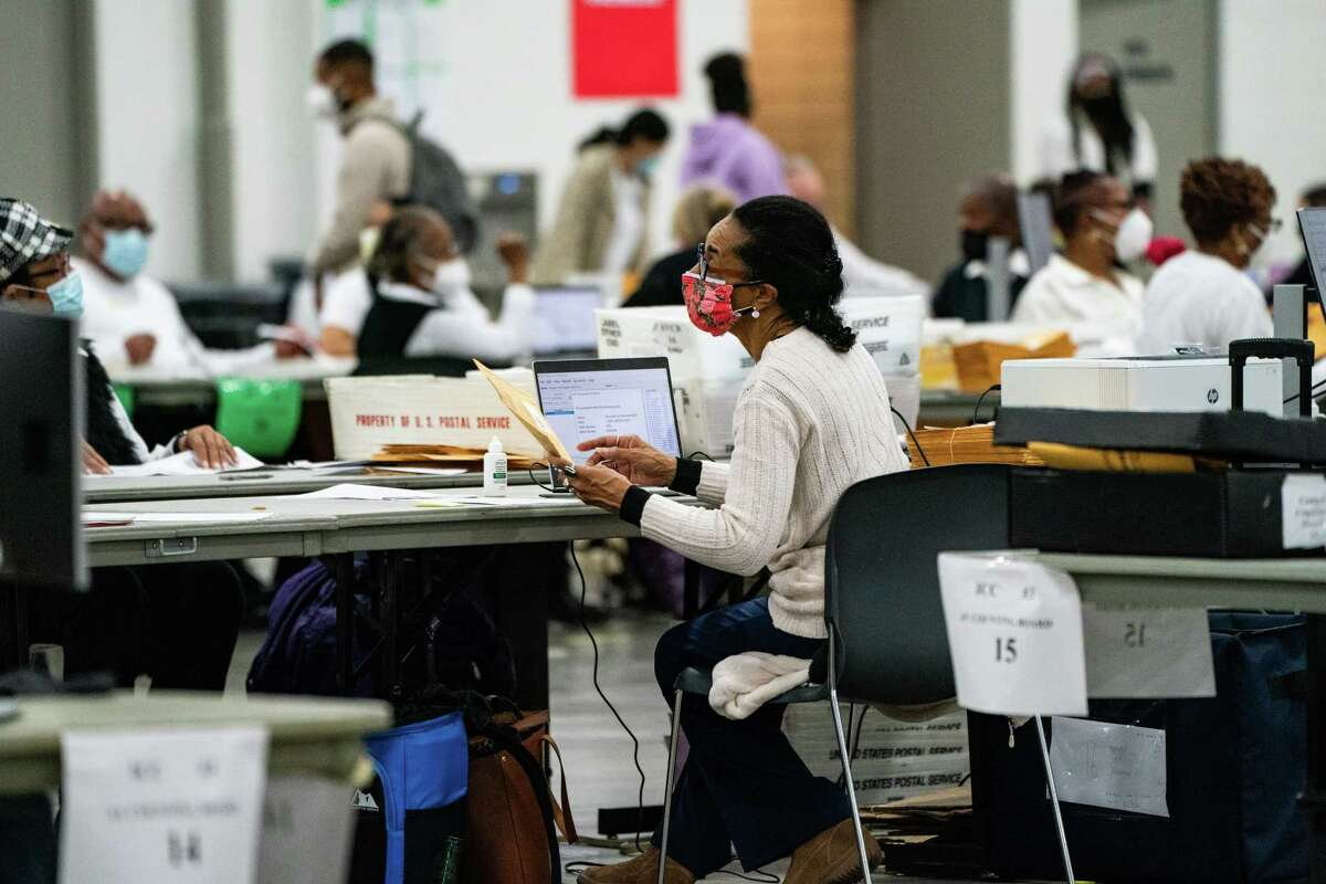 ection workers processes absentee ballots Nov. 4 at the TFC Center in Detroit.