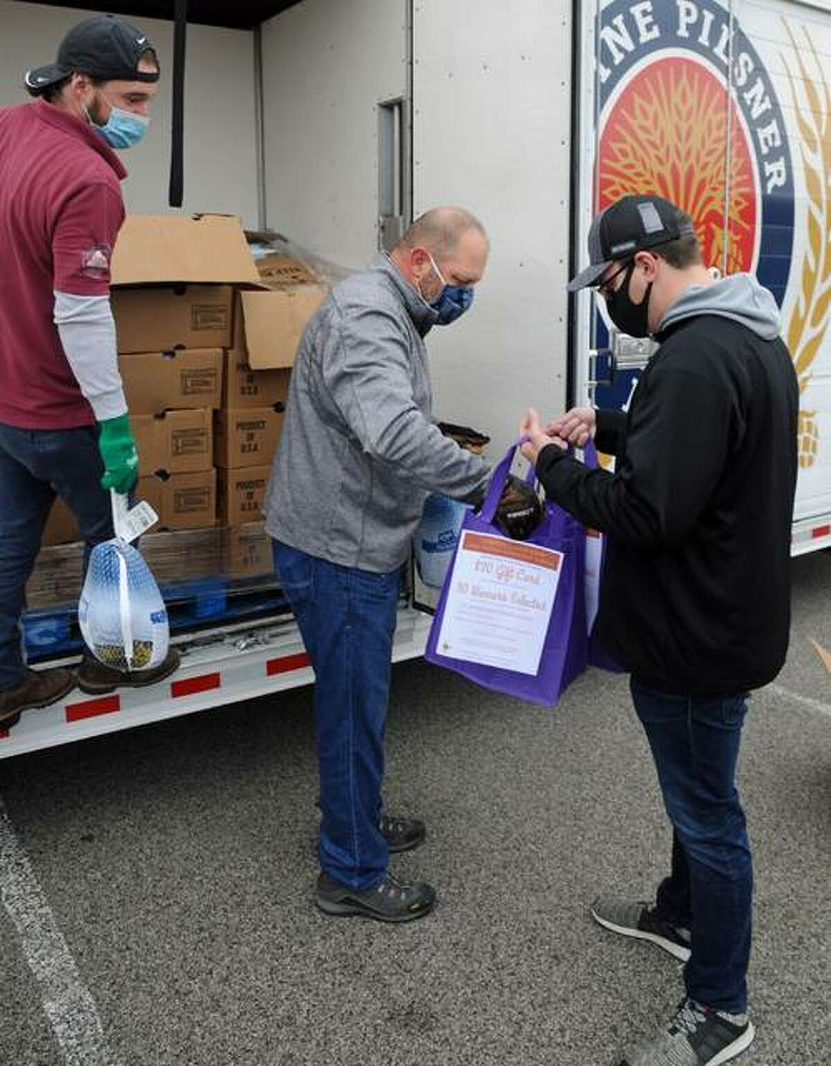 """Employees of Robert """"Chick"""" Fritz Distributing Company hand turkeys from a beer truck to waiting volunteers during Saturday's turkey giveaway in Alton."""