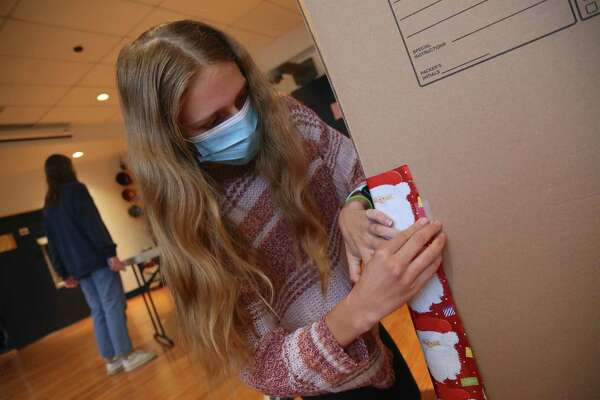 Julianne Teitler, 16, of Darien tapes some wrapping paper onto one of the boxes to be used for The Depot's clothing drive.