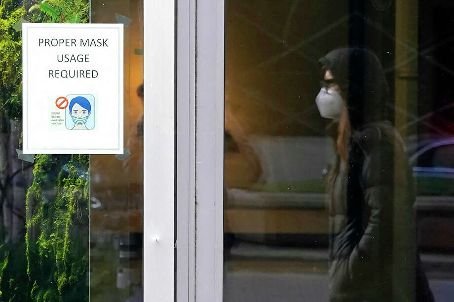 A pedestrian is reflected while walking past a sign reminding people to wear face coverings. An ordinance that would give Jacksonville's mayor authority to mandate mask use in the city is expected to be discussed tonight. Photo: Charles Rex Arbogast   AP / Copyright 2020 The Associated Press. All rights reserved