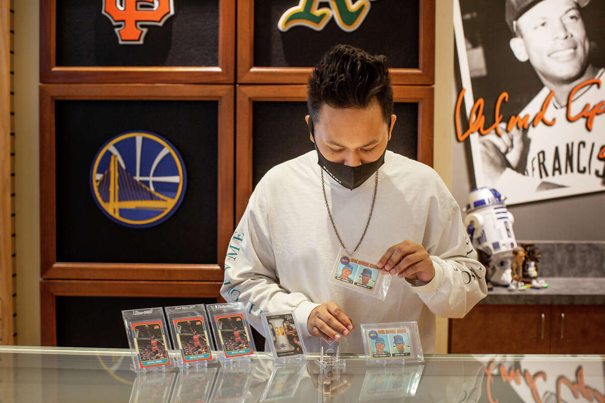 Classic Materials Sports & Collectibles store owner Rey Reyes examines trading cards.
