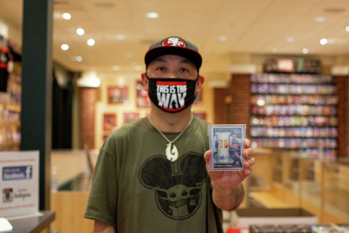 Classic Materials Sports & Collectibles employee D.J. Jue holds up a Stephen Curry trading card. Classic Materials is located in Stonestown Galleria, San Francisco.