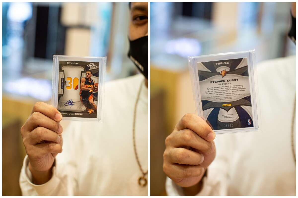 Classic Materials Sports & Collectibles store owner Rey Reyes holds up a Stephen Curry trading card.