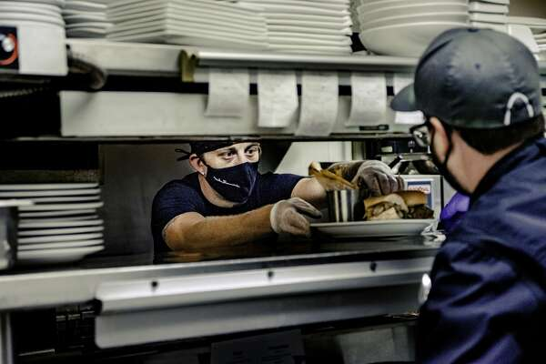 A line cook at Mike Shannon's Grill hands food through the window for general manager Travis Dudley to inspect before heading to a customer Friday afternoon.