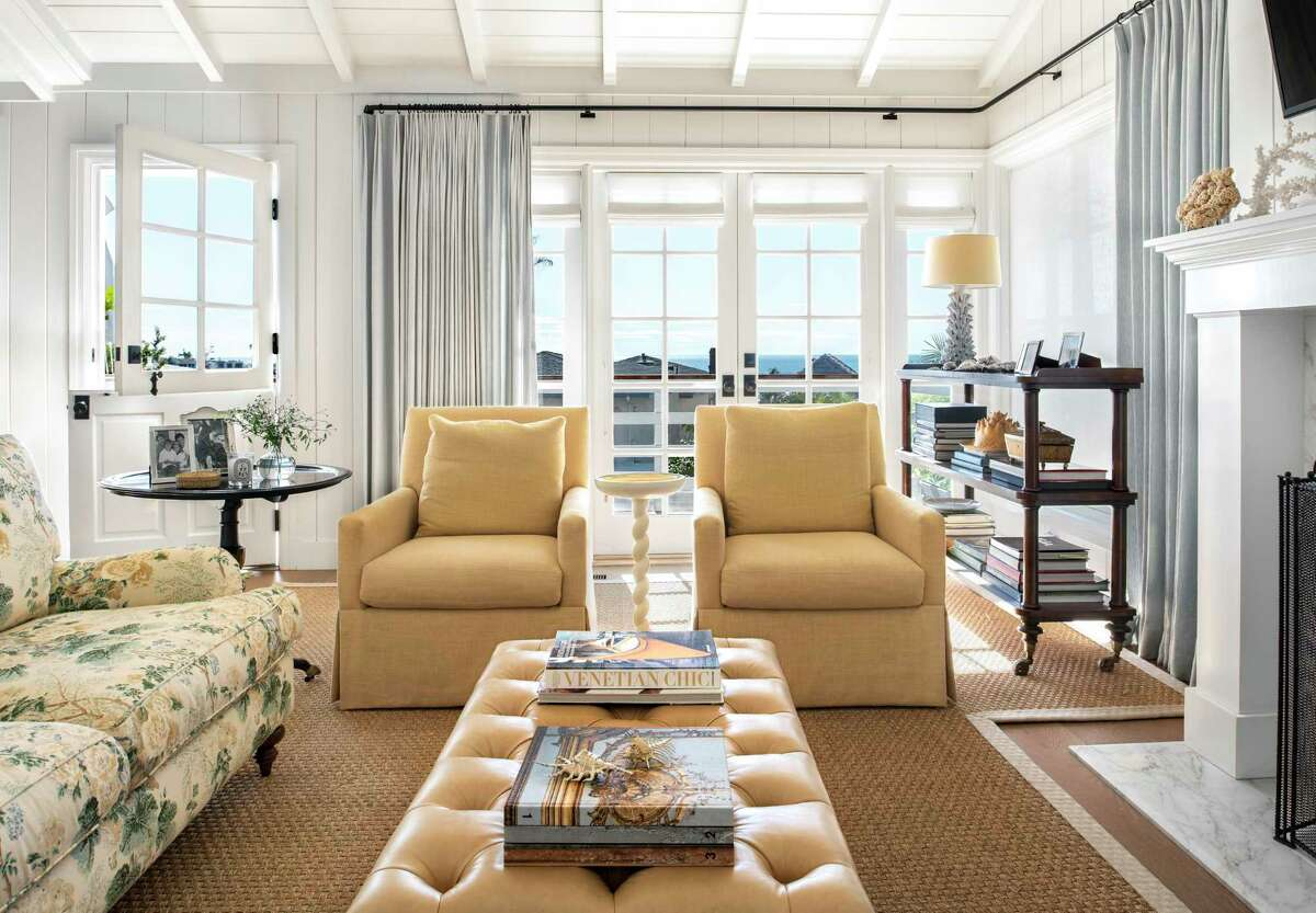 This living room designed by Marea Clark features a floral patterned sofa, multipane windows and a beamed ceiling.