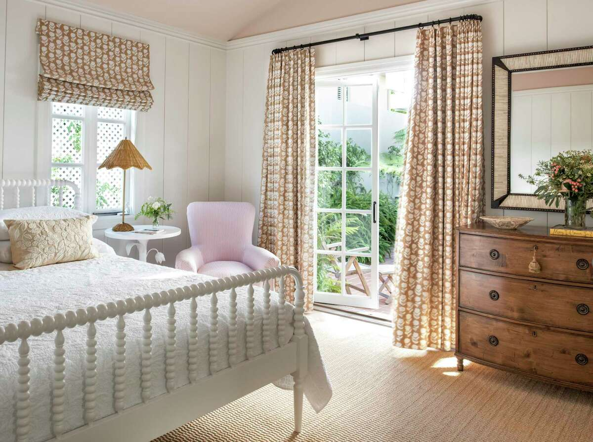 This bedroom designed by Marea Clark includes glass doors that open to a patio.