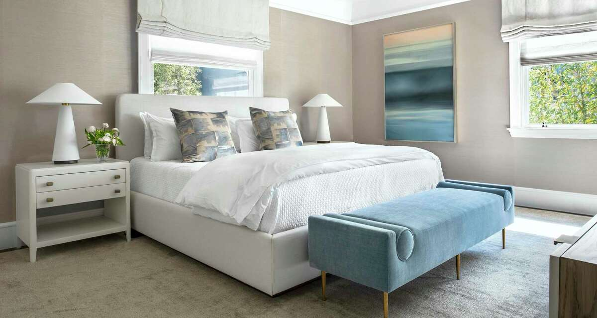 This contemporary bedroom designed by Marea Clark includes modern light fixtures and neutral tones.