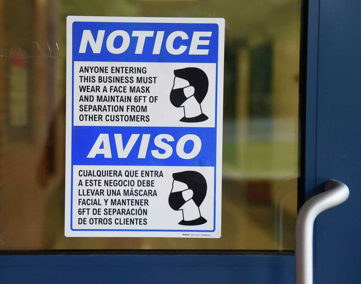 A sign requires students, teachers, and guests to wear face masks at a school in Stamford, Conn. Tuesday, Sept. 1, 2020.