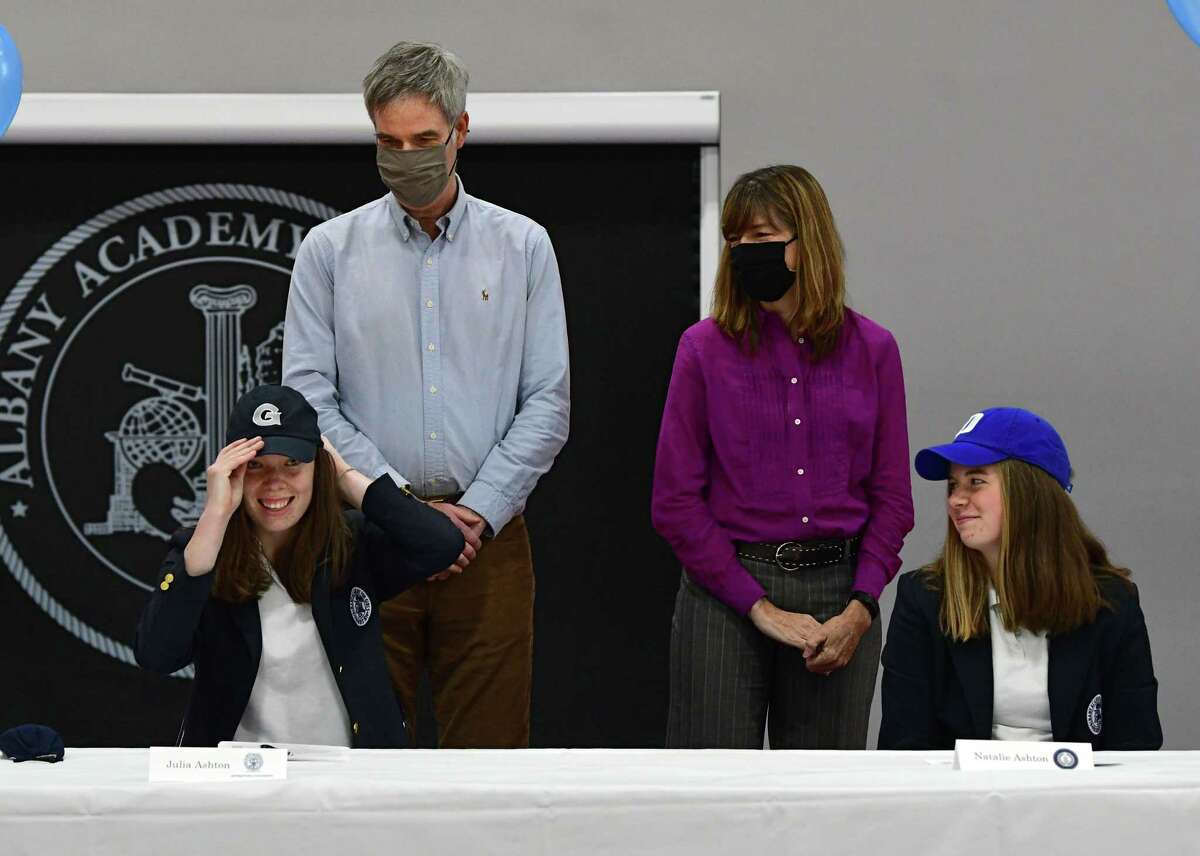 Albany Academy rower Julia Ashton puts on a Georgetown hat after signing a letter of intent for Georgetown University during a college signing ceremony at Albany Academy on Monday, Nov. 23, 2020 in Albany, N.Y. Natalie's sister Natalie, who was signing to row at Duke, sits next to her at right. (Lori Van Buren/Times Union)