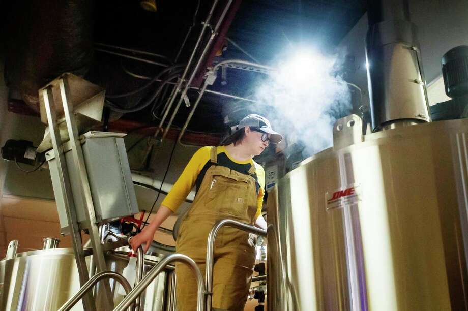 Leah Witkoske, a brewer at Midland Brewing Company, peers down into a boil kettle as she brews a batch of beer Thursday, March 5, 2020 at Midland Brewing Company. (Katy Kildee/kkildee@mdn.net)