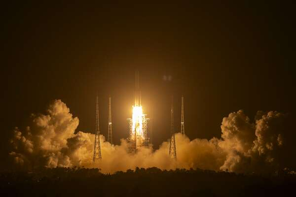 A Long March-5 rocket carrying the Chang'e 5 lunar mission lifts off at the Wenchang Space Launch Center in Wenchang in southern China's Hainan Province, early Tuesday, Nov. 24, 2020. (AP Photo/Mark Schiefelbein)