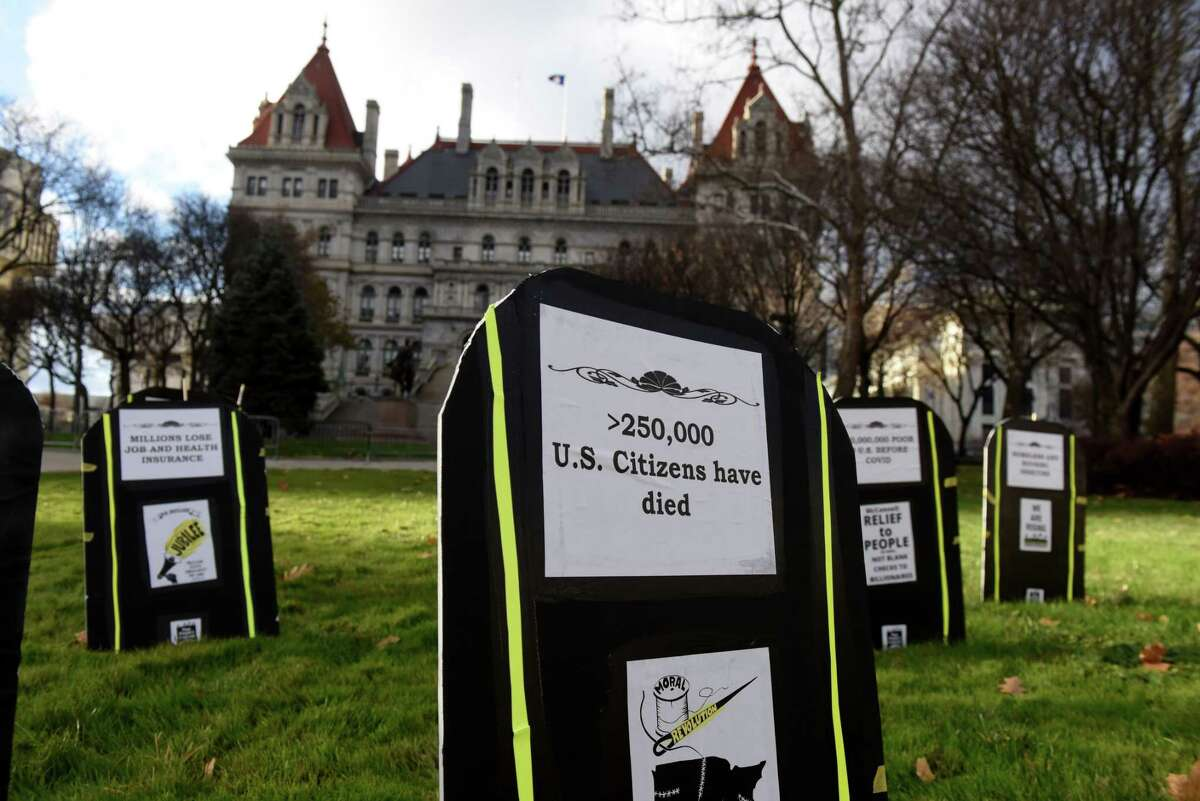 Symbolic tombstones representing the social impacts of coronavirus are placed in West Capitol Park during a Poor People's Campaign stop at the Capitol on Monday, Nov. 23, 2020, in Albany, N.Y. Citizen Action of New York led the Capital Region segment of nationwide event held at state capitols to mourn the nearly quarter-million Americans who died from COVID-19. Organizers are calling for a just recovery from state and national leaders. (Will Waldron/Times Union)