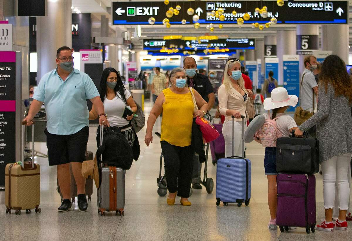 Travelers wearing protective face masks walking through Concourse D at the Miami International Airport on Sunday, November 22, 2020 in Miami, Florida. With the coronavirus surging out of control, the nation's top public health agency pleaded with Americans not to travel for Thanksgiving and not to spend the holiday with people from outside their household. (David Santiago/Miami Herald/TNS)