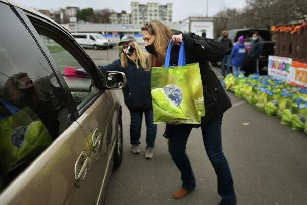 Person-to-Person CEO Nancy Coughlin delivers a frozen Thanksgiving turkey to a waiting car during the Stamford Downtown Parade Spectacular Giving Float turkey giveaway on Bedford Street in Stamford, Conn. on Sunday, November 22, 2020. Stamford Downtown partnered with Person-to-Person, ShopRite, New Wave Seafood, and the Connecticut Office of Tourism to provide Thanksgiving meals to 500 Stamford families.