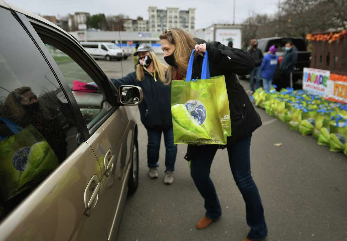 Person-to-Person CEO Nancy Coughlin delivers a frozen Thanksgiving turkey to a waiting car during the Stamford Downtown Parade Spectacular Giving Float turkey giveaway on Bedford Street in Stamford on Sunday, Nov. 22.