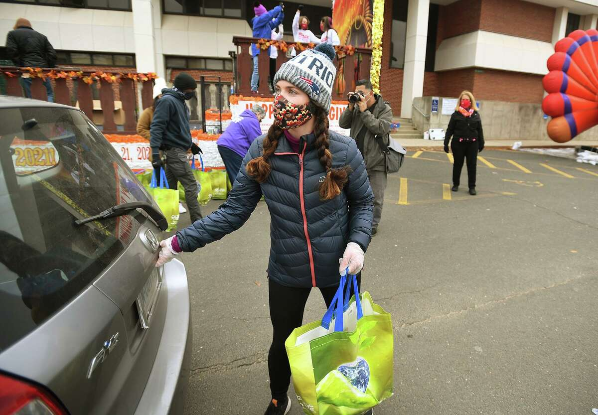 Kate Cook, of Stamford, delivers a frozen Thanksgiving turkey to a waiting car during the Stamford Downtown Parade Spectacular Giving Float turkey giveaway on Bedford Street in Stamford, Conn. on Sunday, November 22, 2020. Stamford Downtown partnered with Person-to-Person, ShopRite, New Wave Seafood, and the Connecticut Office of Tourism to provide Thanksgiving meals to 500 Stamford families.