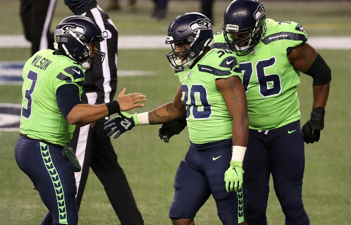 SEATTLE, WASHINGTON - NOVEMBER 19: Carlos Hyde #30 of the Seattle Seahawks is congratulated by Russell Wilson #3 after he ran in for a touchdown against the Arizona Cardinals in the third quarter at Lumen Field on November 19, 2020 in Seattle, Washington. (Photo by Abbie Parr/Getty Images)
