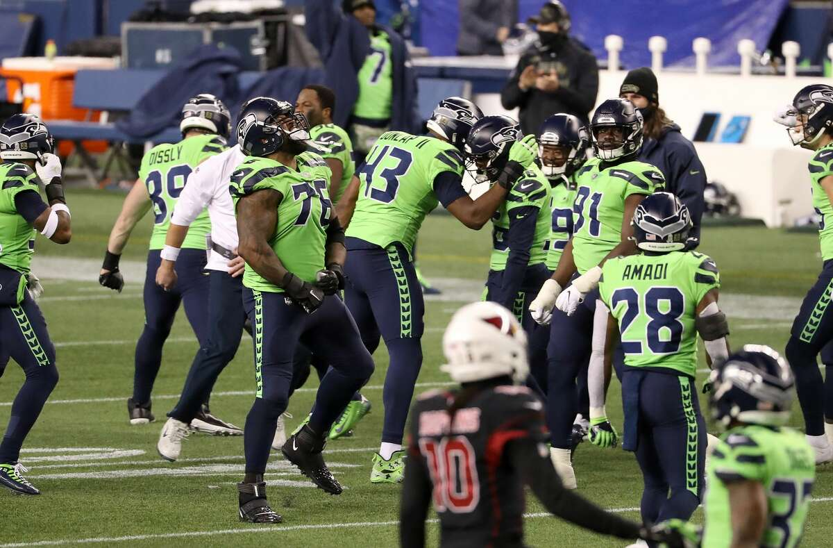SEATTLE, WASHINGTON - NOVEMBER 19: Carlos Dunlap #43 of the Seattle Seahawks is congratulated by teammates after he sacked Kyler Murray #1 of the Arizona Cardinals in the final minute of their game at Lumen Field on November 19, 2020 in Seattle, Washington. (Photo by Abbie Parr/Getty Images)
